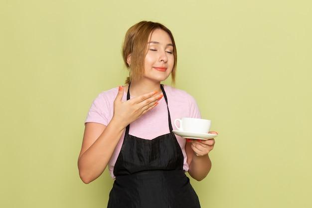 Вид спереди молодой девушки-парикмахера в розовой футболке и черной накидке с чашкой, улыбаясь на зеленом Бесплатные Фотографии