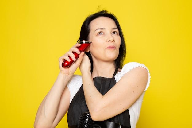 Вид спереди молодая женщина-парикмахер в белой футболке черная накидка с использованием механических волос машинная укладка волос Бесплатные Фотографии