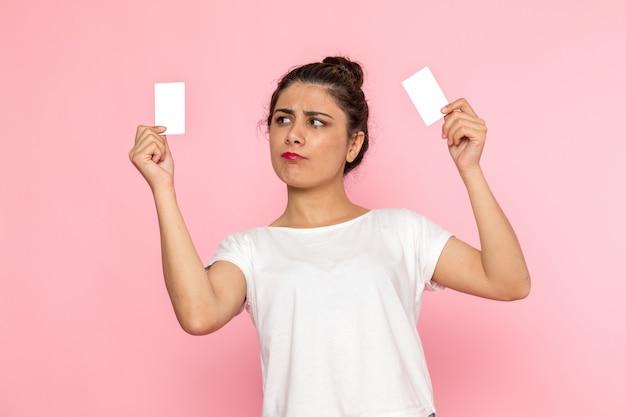白いtシャツとブルージーンズの白いカードを保持している正面の若い女性 無料写真