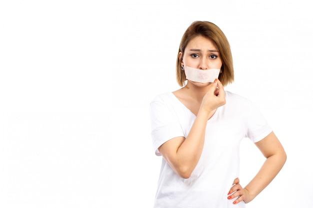 白の彼女の包帯に触れる彼女の口の周りに白い包帯の白いtシャツの正面図の若い女性 無料写真