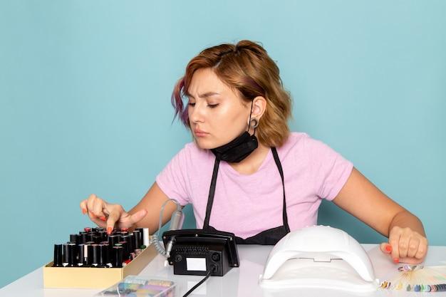 正面図の若い女性のマニキュアピンクのtシャツに黒い手袋とテーブルの前に座っている黒いマスクブルーのマニキュアをチェック 無料写真