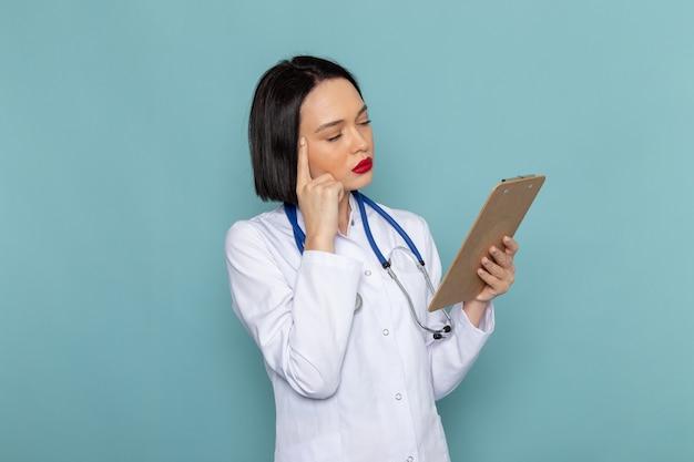 青い机医学病院医師にメモ帳を保持している白い医療スーツ青い聴診器で正面の若い女性看護師 無料写真