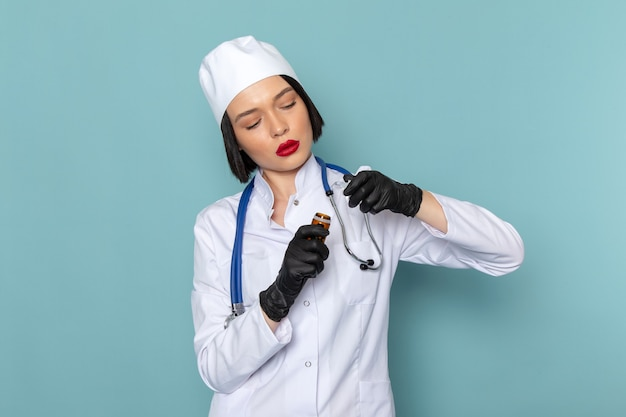 白い医療スーツと青い机の医学病院の医師に薬を保持している青い聴診器で正面の若い女性看護師 無料写真