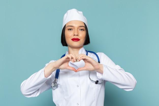 白い医療スーツと青い机の医学病院の医師に心のサインを示す青い聴診器で正面の若い女性看護師 無料写真