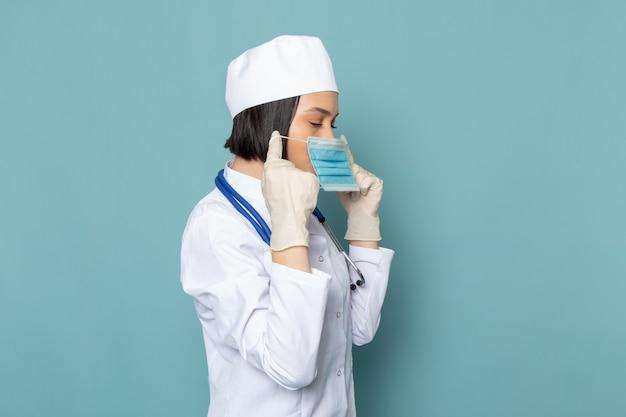 Вид спереди молодая медсестра в белом медицинском костюме и синем стетоскопе в маске на синем столе врача больницы Бесплатные Фотографии