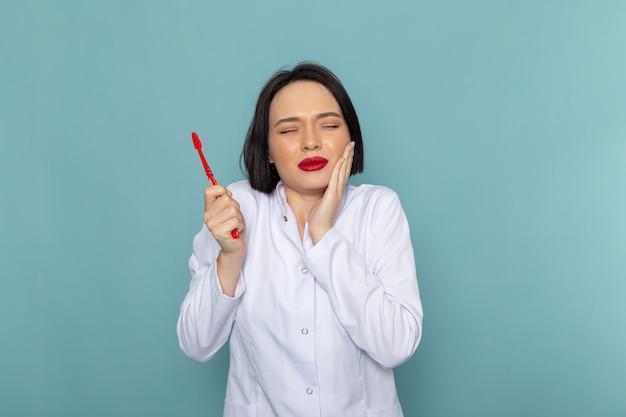 Вид спереди молодая медсестра в белом медицинском костюме с зубной болью на синем столе врача больницы Бесплатные Фотографии