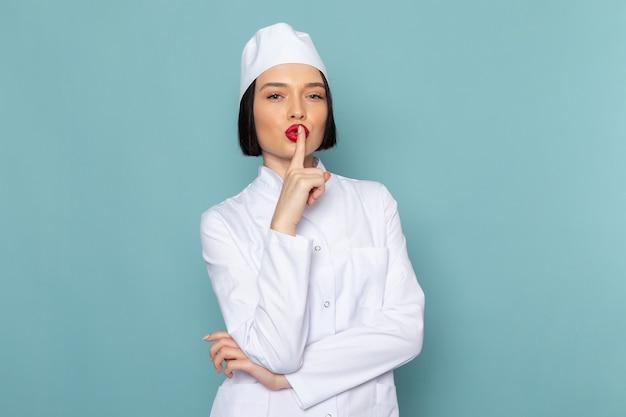 Вид спереди молодая медсестра в белом медицинском костюме позирует и показывает знак тишины на синем столе врача больницы Бесплатные Фотографии