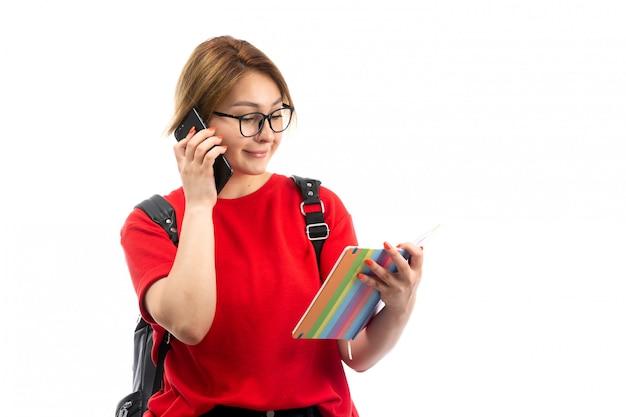 コピーブックを保持している黒いバッグと白を話している黒いスマートフォンを身に着けている赤いtシャツの正面の若い女性学生 無料写真