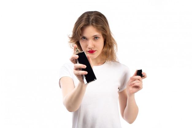 白に黒の香水管を保持している白いtシャツの正面の若い女性 無料写真