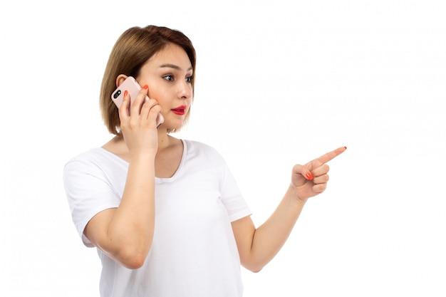 白の電話で話しているポーズをとって白いtシャツで正面の若い女性 無料写真