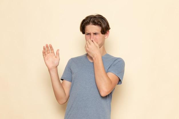 Молодой мужчина в серой футболке, закрывающей нос, вид спереди Бесплатные Фотографии