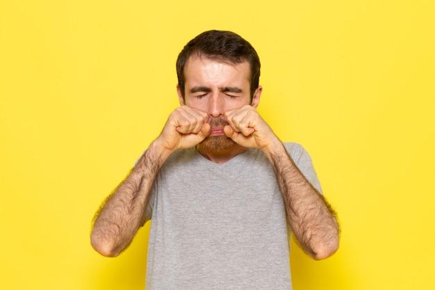 黄色の壁の男カラーモデル感情服で泣いている灰色のtシャツの偽の正面の若い男性 無料写真