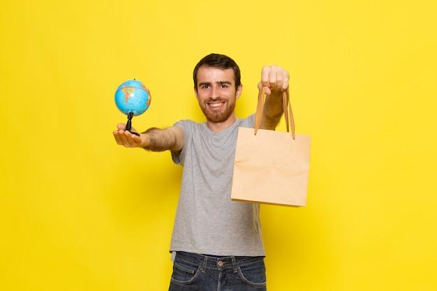 小さなグローブと黄色の壁の男の表情感情カラーモデルに笑顔でパッケージを保持している灰色のtシャツの正面の若い男性 無料写真