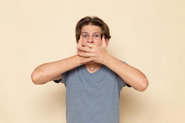Молодой мужчина в серой футболке позирует, закрывая рот, вид спереди Бесплатные Фотографии