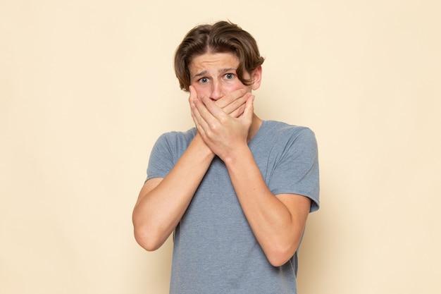 Молодой мужчина в серой футболке, вид спереди, позирует, держа рот Бесплатные Фотографии