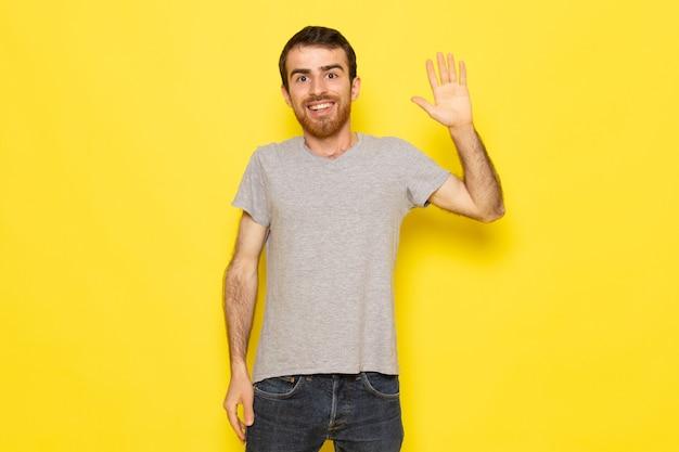 黄色の壁の男の表情感情カラーモデルに上げられた手で灰色のtシャツの正面の若い男性 無料写真