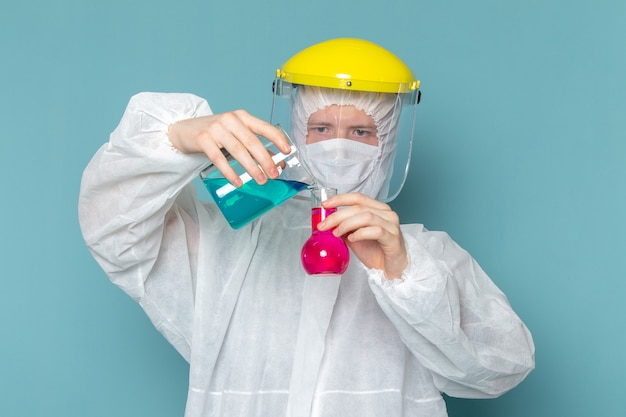 青い壁の男のスーツの特別な機器の色の危険にソリューションを混合する白い特別なスーツの正面図の若い男性 無料写真
