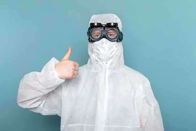 青い壁の男のスーツの特別な装備の色に大きな兆候を示す白い特別なスーツの正面の若い男性 無料写真