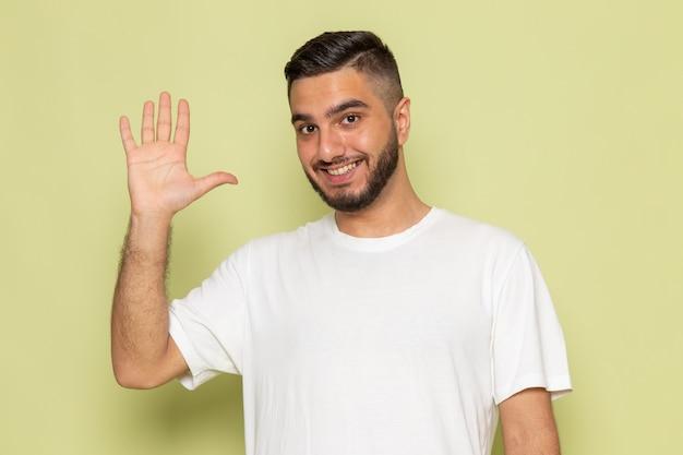 白いtシャツの正面の若い男性が挨拶し、笑顔 無料写真