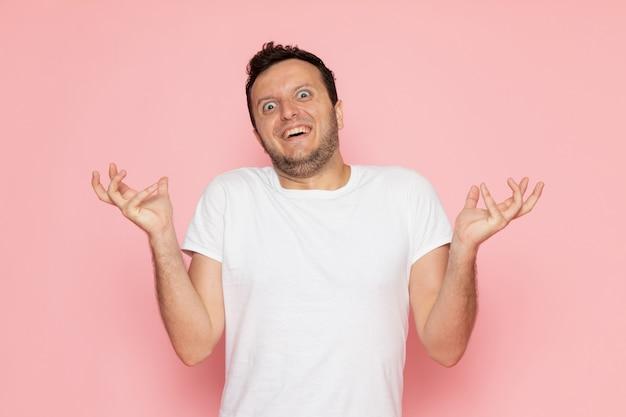 Молодой мужчина в белой футболке, вид спереди, позирует с забавным выражением лица Бесплатные Фотографии
