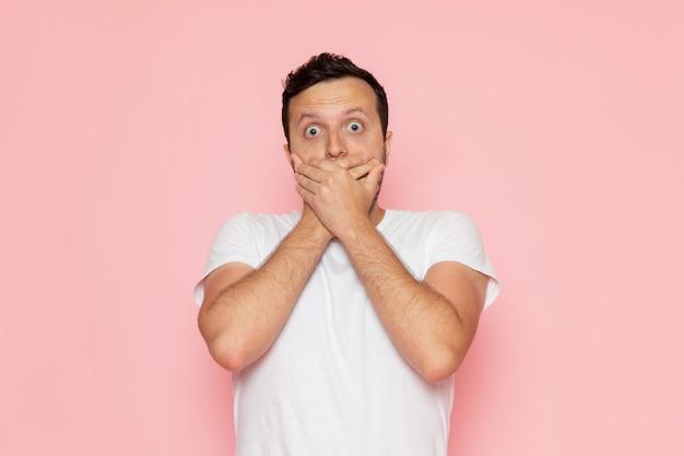 Молодой мужчина в белой футболке, вид спереди, позирует с шокированным выражением лица Бесплатные Фотографии
