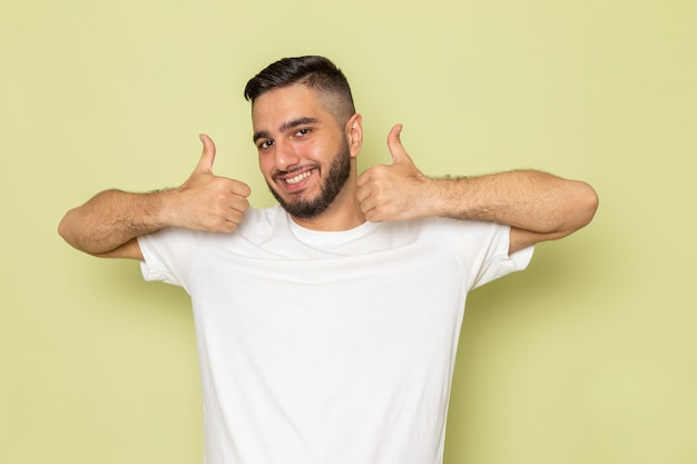 笑顔で兆候のような白いtシャツを着た正面の若い男性 無料写真