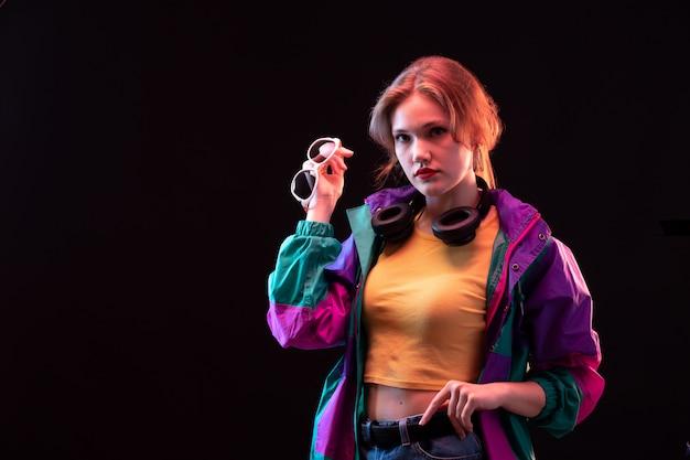 검은 이어폰과 선글라스 포즈와 화려한 코트 오렌지 티셔츠에 전면보기 젊은 현대 아가씨 무료 사진