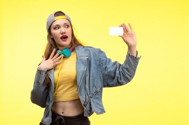 Вид спереди молодая современная женщина в желтой рубашке черных брюк и джинсовой куртке с цветными наушниками держит белую карточную позу Бесплатные Фотографии