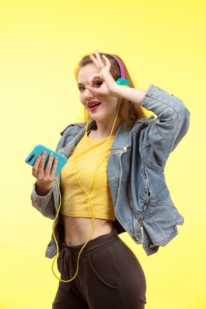 음악을 듣고 컬러 이어폰과 노란색 셔츠 검은 바지와 진 코트의 전면보기 젊은 현대 여성 무료 사진