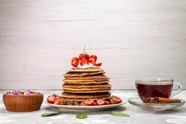 前面のおいしいフルーツケーキにクリームティーと赤いイチゴのおいしい丸いパンケーキ 無料写真