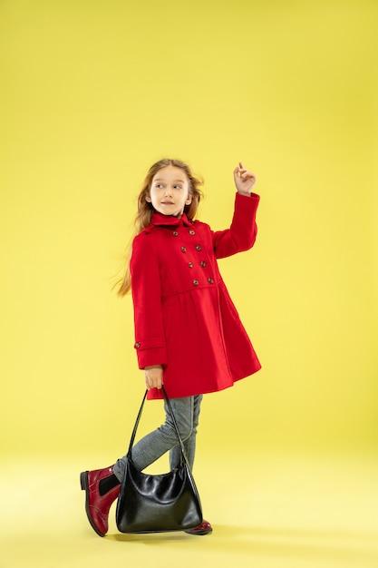 黄色のスタジオの壁に黒いバッグを保持している赤いレインコートの明るいファッショナブルな女の子の全身像 無料写真