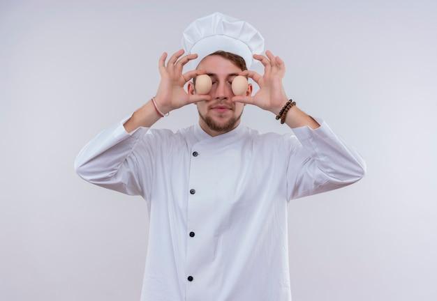 白い炊飯器の制服と白い壁に彼の目の前に有機卵を保持している帽子を身に着けている面白い若いひげを生やしたシェフの男 無料写真