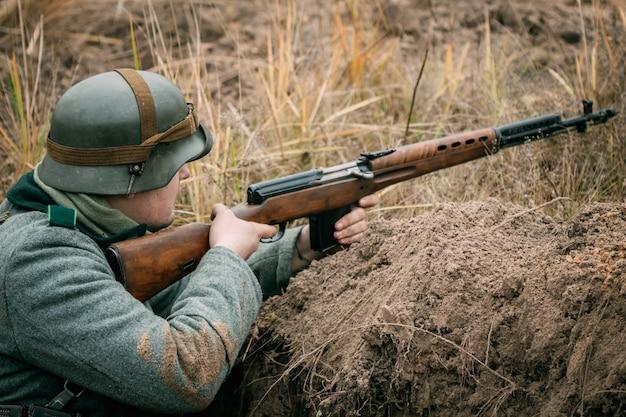 Немецкий солдат с советской винтовкой в окопе Premium Фотографии