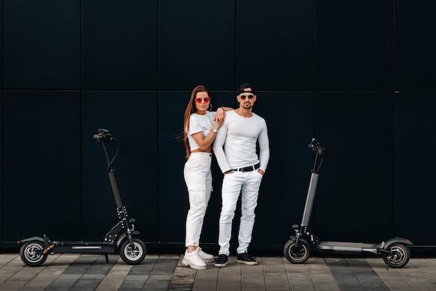 少女と男が街中の電動スクーターを歩いており、カップルはスクーターに恋をしています。 Premium写真
