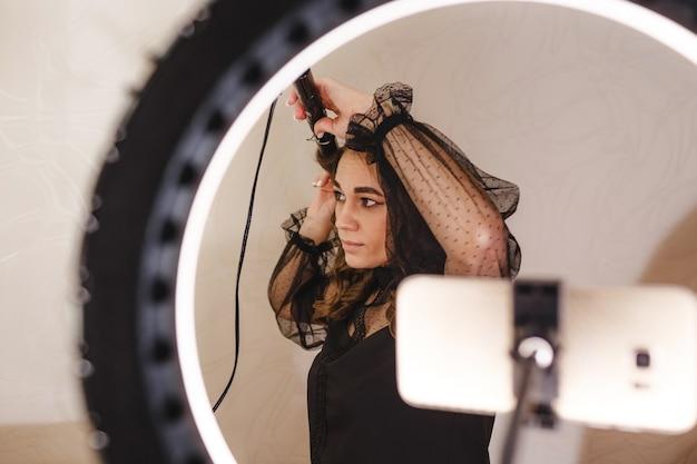 Девушка-блогер-парикмахер снимает на телефон видео и рассказывает своим зрителям, как правильно делать прически. Premium Фотографии