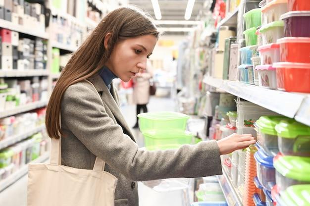 Девушка выбирает контейнер для еды в супермаркете. Premium Фотографии