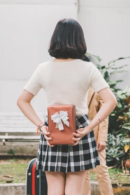 Девушка, скрывающая подарок за сюрпризом, за спиной Premium Фотографии