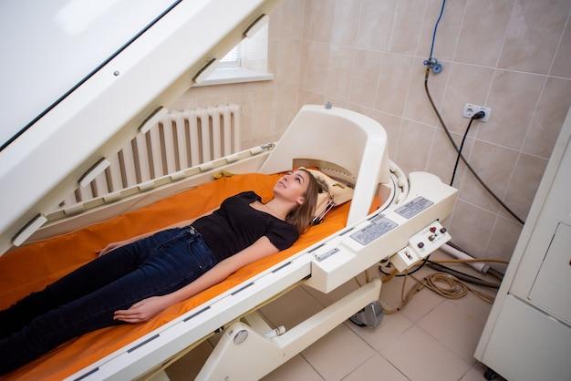 Девушка в черной футболке лежит в гипербарической камере, кислородная терапия Premium Фотографии