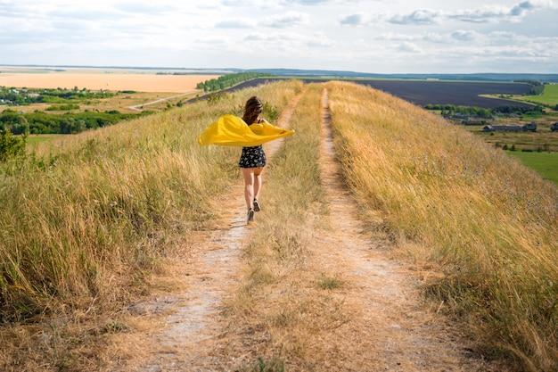 Девушка в платье и развевающейся на ветру желтой накидке бежит по сельской тропе Premium Фотографии