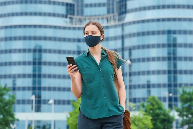 시내에서 바지 주머니에 손을 밀어 스마트 폰을 들고 얼굴 마스크에 여자 프리미엄 사진
