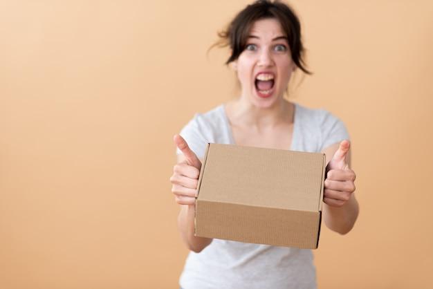 グレーのtシャツを着た女の子がブランドボックスを手に持って感情的に叫び、ベージュのスペースに親指を現している Premium写真