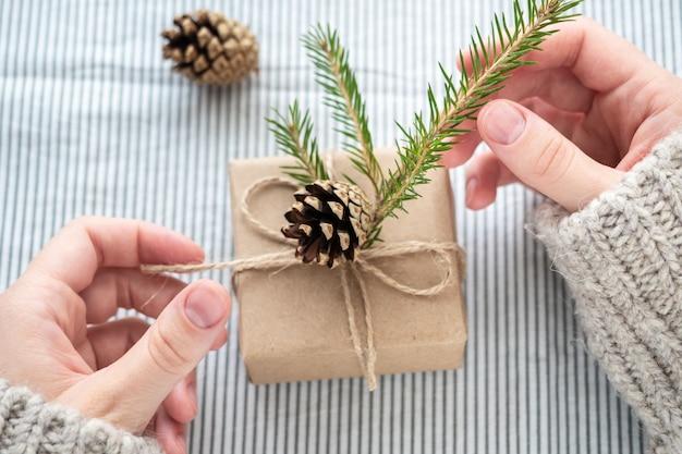 스웨터를 입은 소녀가 자신의 손으로 장식 한 선물을 들고 있습니다. Kraft 종이, 크리스마스 또는 새해로 만든 아름다운 선물 상자. 여자의 손에 선물, 클로즈업. 프리미엄 사진