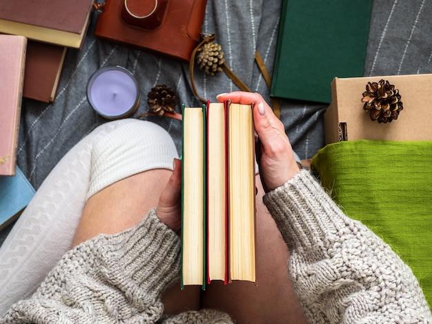 顔のないセーターの女の子が本と毛布の上に座っています Premium写真