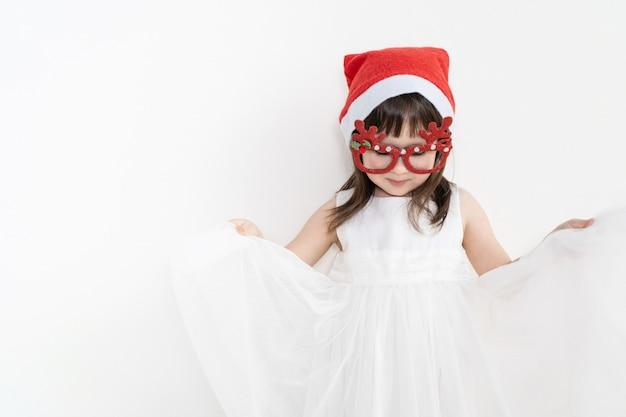 白いドレスの少女が明るい背景に立っています。赤ちゃんはスカートを手に持っています。 Premium写真