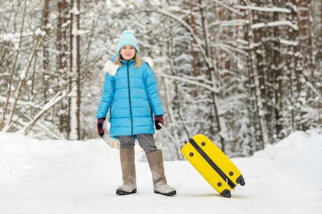 冬のフェルトブーツを履いた女の子は、凍るような雪の日にスーツケースを持って行きます。 Premium写真