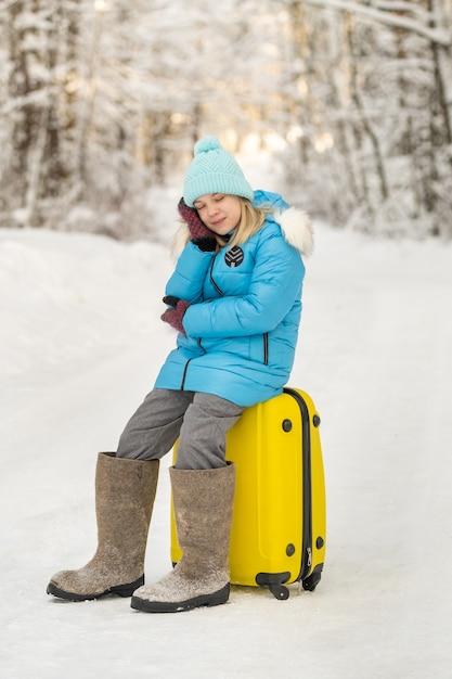 冬のフェルトブーツを履いた女の子が、凍るような雪の日にスーツケースに座っています。 Premium写真