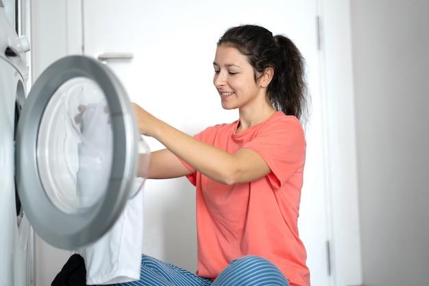女の子がアパートの床に座っている間に汚れた洗濯物を洗濯機に入れます。洗濯日、家事 Premium写真