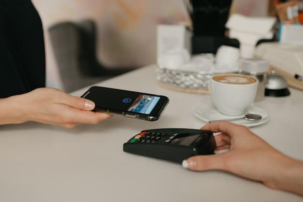 カフェで非接触型nfcテクノロジーを使用してスマートフォンでラテの支払いをしている女の子。女性のバリスタがコーヒーショップのクライアントに支払うための端末を差し出します。 Premium写真
