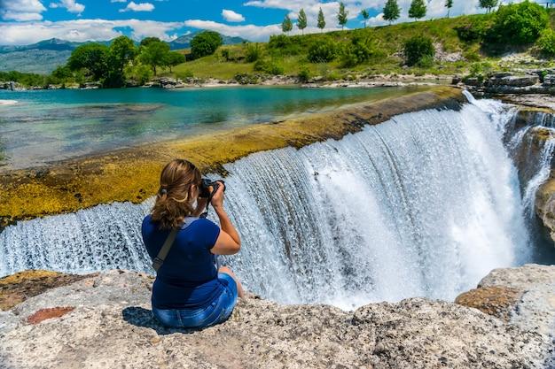 Девушка-фотограф фотографирует ниагарский водопад в черногории. Premium Фотографии