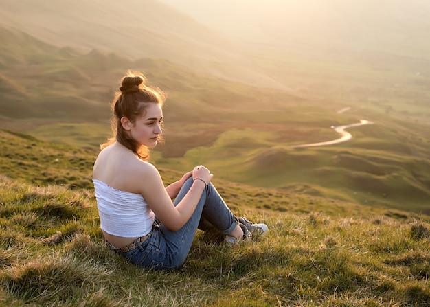 Девушка сидит на вершине холма на фоне удивительного пейзажа на закате летом Premium Фотографии